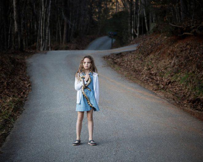 Jennifer Garza-Cuen, _Untitled—Girl with Snake, Rabun, GA_, 2016. Archival pigment print. Courtesy the artist.