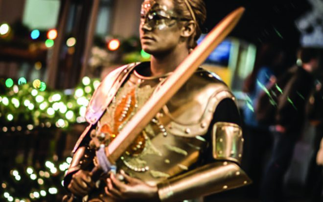 A parader in the 2015 Joan of Arc Parade. Photo by Brandt Vicknair. Image via [Offbeat Magazine](https://www.flickr.com/photos/offbeatmagazine/sets/72157650177097075/).